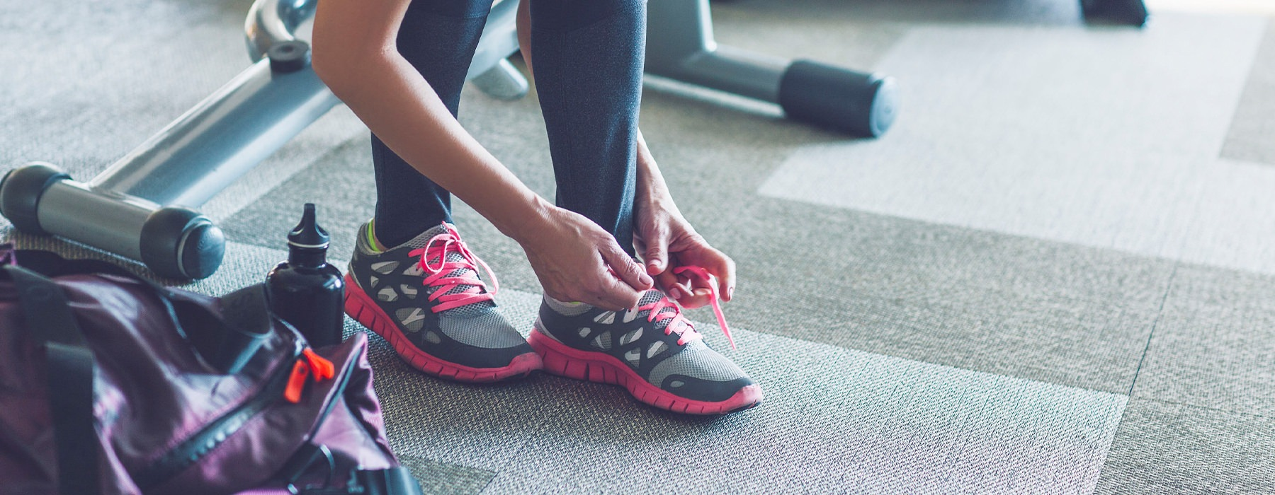 Woman putting on her tennis shoes in the fitness center