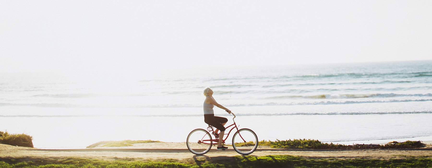 Woman riding her bike by the ocean